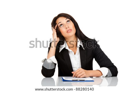 beautiful business woman sitting at the desk think looking up point finger to empty copy space, isolated over white background