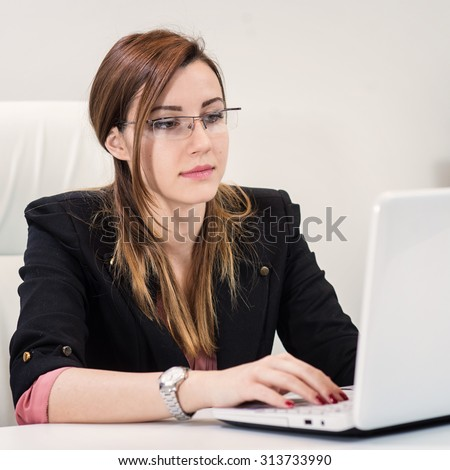 Beautiful business woman sitting in office and typing on laptop. - stock photo