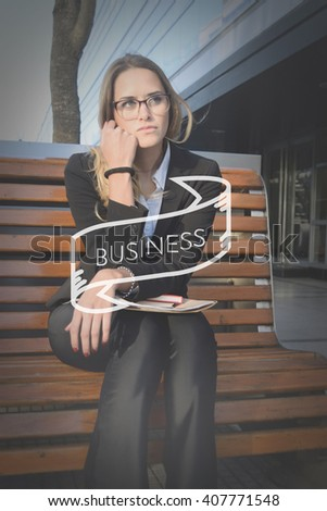 Beautiful business woman sitting on a bench outside her office with business text. - stock photo