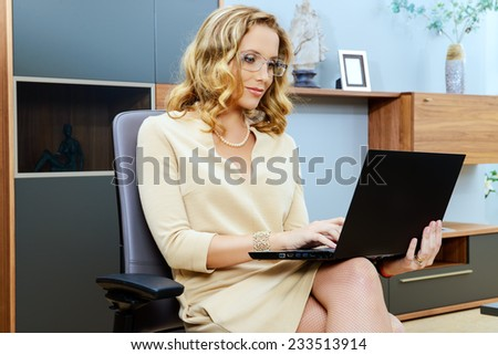 Beautiful business woman sitting on a chair and working on her laptop. - stock photo