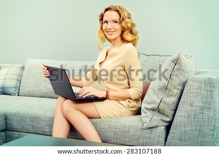 Beautiful business woman sitting on a couch and working on a laptop. - stock photo