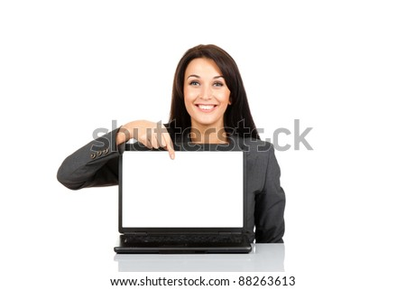 beautiful business woman smile sitting at the desk looking at camera, point finger at isolated white laptop screen over white background - stock photo