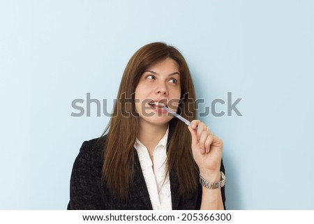 Beautiful business woman smiling and thinking, biting on a pen. Copy space to the left, right and above  - stock photo