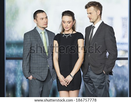 Beautiful business woman standing ashamed surrounded by two business colleagues who are watching her and judging her - concept - stock photo