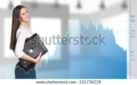 Beautiful business woman stands behind the big graph on the office background. - stock photo