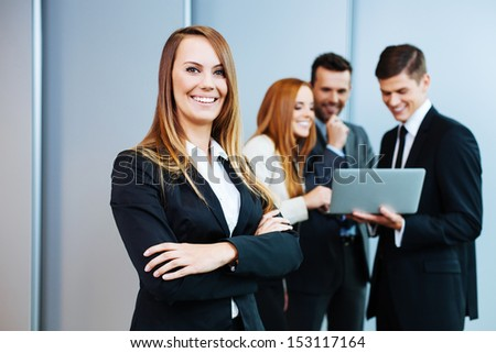 Beautiful business woman stands on the front of business partners.
