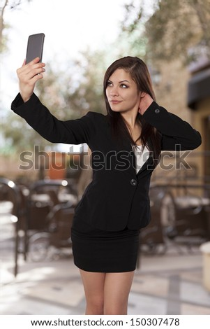Beautiful business woman takes a selfie with her cell phone.