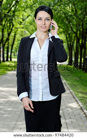 Beautiful business woman talking cell phone and walking in the park - stock photo