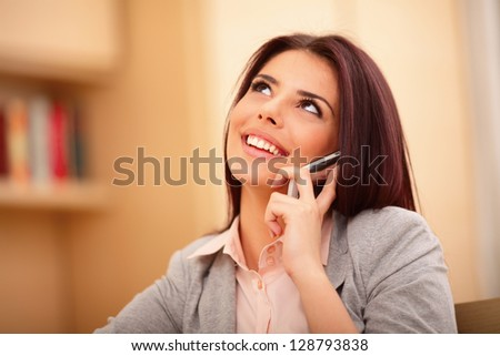 Beautiful business woman talking on cell phone and looking at copyspace - stock photo