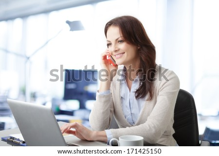 Beautiful business woman talking on mobile phone - stock photo