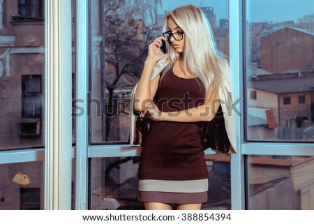 beautiful business woman talking on the phone by the window overlooking the city. Business woman talking phone. City views behind the window in the office. Business concept. - stock photo