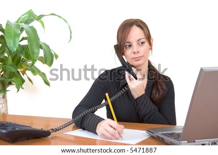 Beautiful business woman talking on the phone in her office