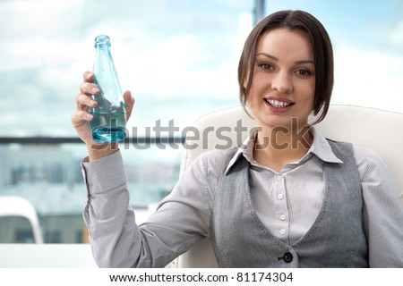 Beautiful business woman thinking about something while drinking cool fresh mineral water at her office - stock photo