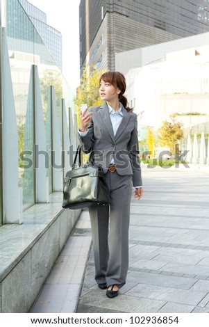 Beautiful business woman walking outside her office. Portrait of - stock photo