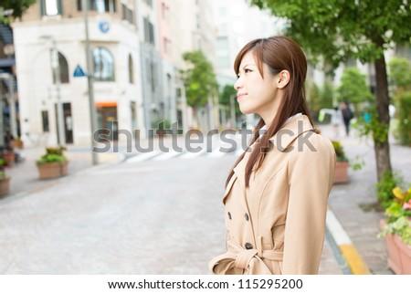 Beautiful business woman walking outside her office. Portrait of asian. - stock photo