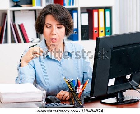 Beautiful business woman while working on computer at her office - stock photo
