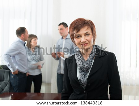 Beautiful business woman with colleagues discussing in the background.