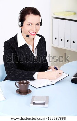 Beautiful business woman with headphones and microphone is sitting behind desk.