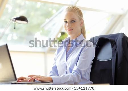 Beautiful business woman with laptop - stock photo