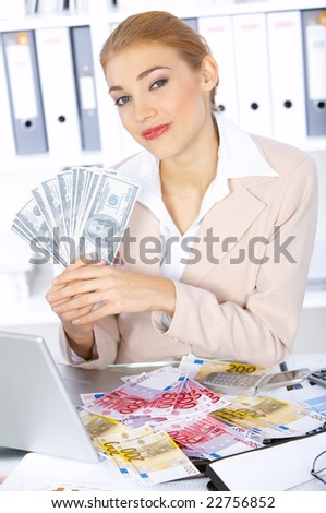 Beautiful business woman with lots of cash on table - stock photo
