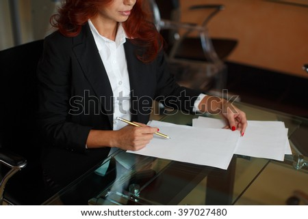 Beautiful business woman working with papers sitting at the Desk in the office - stock photo