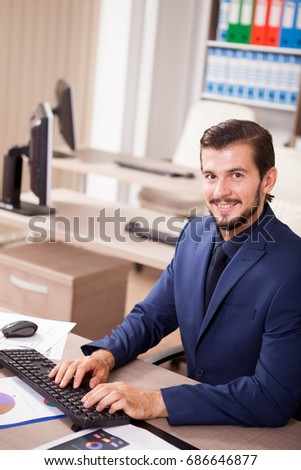 Beautiful Businessman in suit working in his office. Business and corporate. Image of young succesful entrepreneur at his work place.