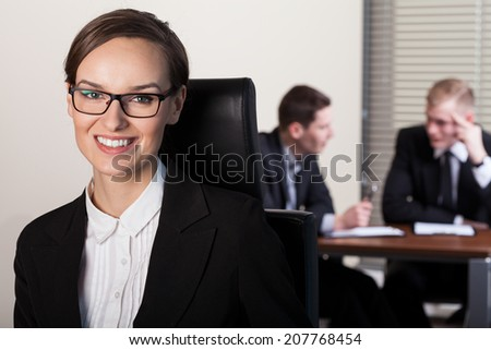 Beautiful businesswoman and co-workers in office, horizontal