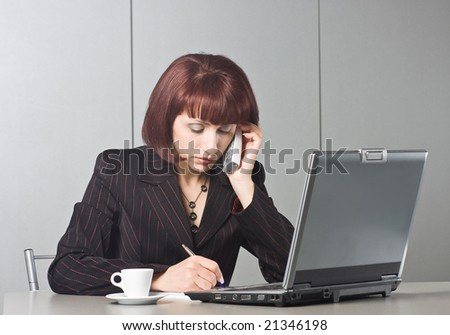 Beautiful businesswoman behind a desktop and a laptop speaks on the phone