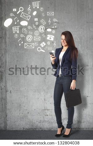 Beautiful businesswoman browsing internet with smart phone. Young businesswoman standing against grunge background - stock photo