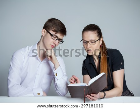 Beautiful businesswoman discussing schedule with bored clerk