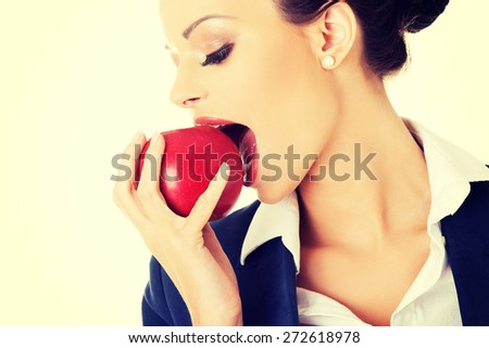 Beautiful businesswoman eating an apple - stock photo