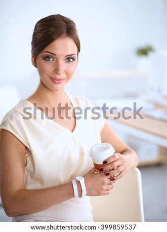 Beautiful  businesswoman enjoying coffee in bright office