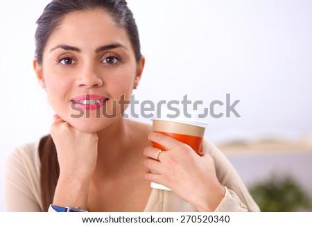 Beautiful  businesswoman enjoying coffee in bright office, sitting - stock photo