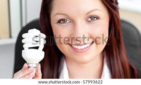Beautiful businesswoman holding a light bulb sitting on her chair in her office - stock photo