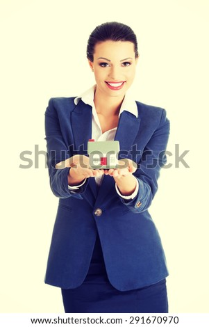 Beautiful businesswoman holding a model of house - stock photo