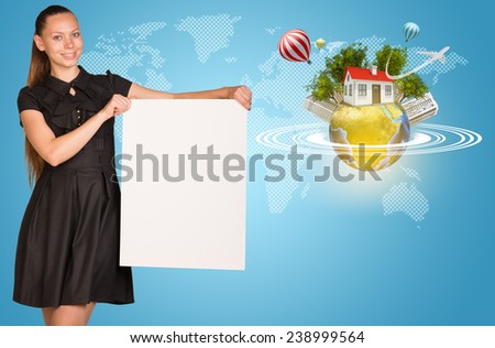 Beautiful businesswoman holding blank paper sheet. Beside is miniature Earth with trees, small house, high-rise buildings, air balloons, airplane, and surrounded by rings.  Contoured world map as - stock photo
