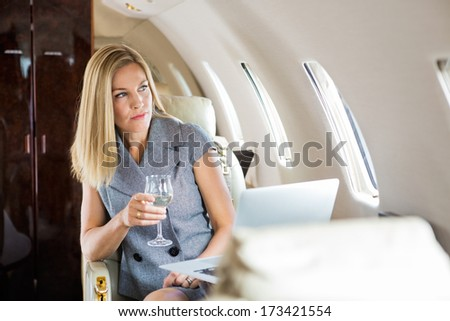 Beautiful businesswoman holding wineglass while looking through window of private jet - stock photo