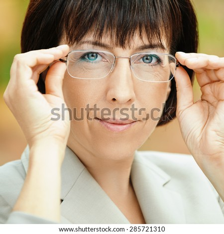 Beautiful businesswoman in bright suit adjusts glasses. - stock photo
