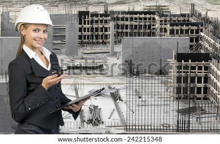 Beautiful businesswoman in suit and helmet holding paper holder and portable radio. Construction site in background. Building concept - stock photo