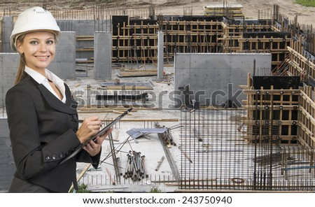 Beautiful businesswoman in suit and helmet holding paper holder and writing. Construction site in background. Building concept - stock photo