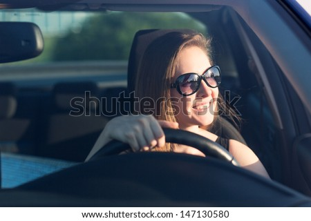Beautiful businesswoman in sunglasses driving her car - stock photo