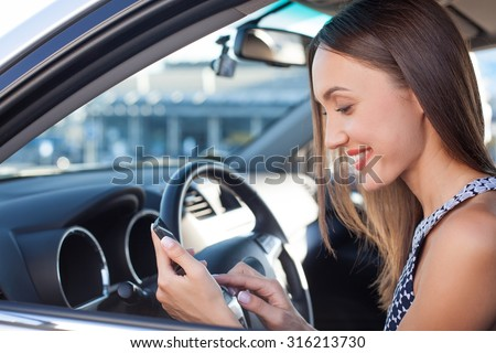 Beautiful businesswoman is driving her personal vehicle. She is sitting at the steering wheel and smiling. The lady is holding a mobile phone and messaging to her friend - stock photo