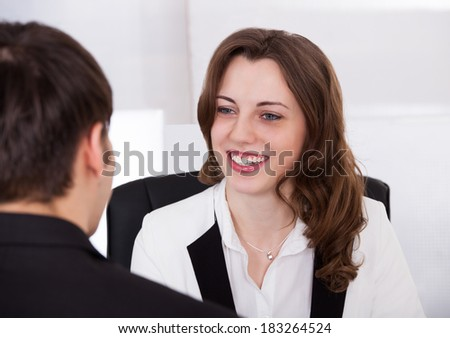 Beautiful businesswoman looking at male candidate during interview in office - stock photo