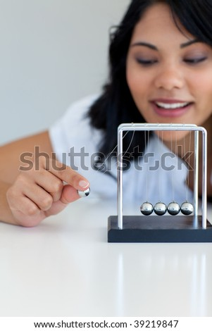 Beautiful businesswoman moving kinetic balls in office - stock photo