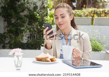 Beautiful businesswoman on her lunch outside at the coffee shop - stock photo