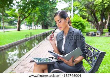 Beautiful businesswoman planning her work in the park