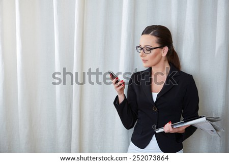 Beautiful businesswoman portrait with a phone in her hand - stock photo