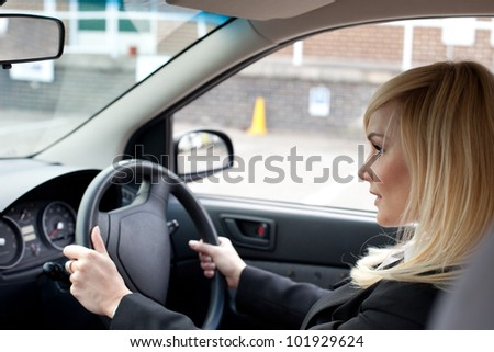 Beautiful businesswoman seated behind the steering wheel driving a ca in an urban environmentr