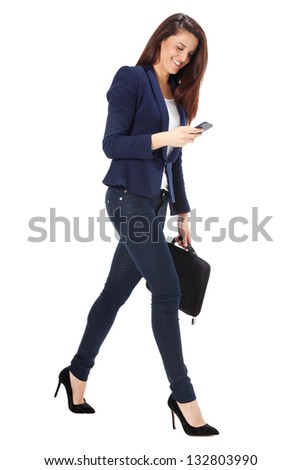 Beautiful businesswoman sending a message on smart phone. Young businesswoman walking. Isolated on white background - stock photo
