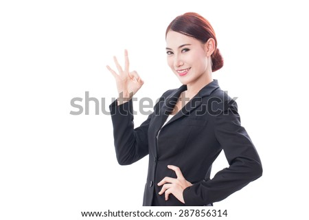 Beautiful businesswoman showing ok sign - stock photo
